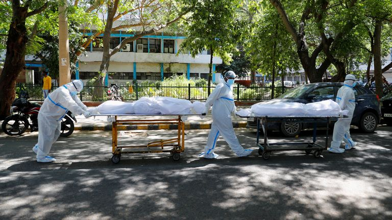 Medical personnel wearing protective equipment (PPE) transport the bodies of people with COVID infection, outside Guru Teg Bahadur Hospital, New Delhi, India