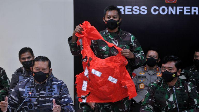 Ein Soldat hält einen Fluchtanzug in der Hand, der vermutlich von der versunkenen indonesischen Marine stammt
