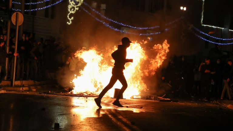 A Palestinian protester runs in front of a burning barricade