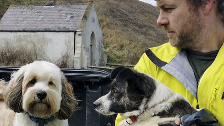 Undated handout photo issued by the RNLI of Ed Thomas and his own pet dog, Ollie, after their rescue operation of the Jack Russell that was found trapped under rocks for three days near Skinningrove in North Yorkshire, after going missing with his owner