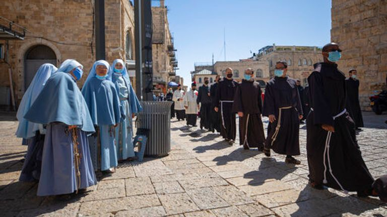 Priests wearing face masks as they march after Easter Sunday mass in the Old City of Jerusalem