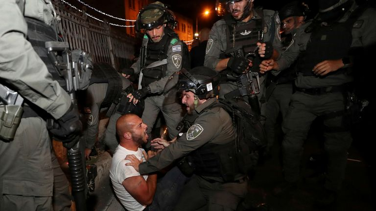 Israeli police detain a Palestinian man as trouble flared again on Friday