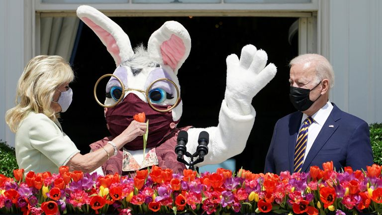 U.S. President Joe Biden stands to deliver his remarks on the tradition of Easter, next to first lady Jill Biden holding a flower and a person wearing an Easter Bunny costume at the Blue Room Balcony of the White House in Washington, U.S. April 5, 2021