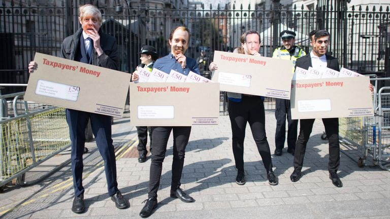 """Labour activists wearing face masks, depicting Prime Minister Boris Johnson, Chancellor Rishi Sunak, Health Secretary Matt Hancock and former prime minister David Cameron, carry oversized envelopes addressed to """"Tory chums, Dodgy contracts, Jobs for mates"""" as the Labour party highlight Tory sleaze and cronyism outside Downing Street"""