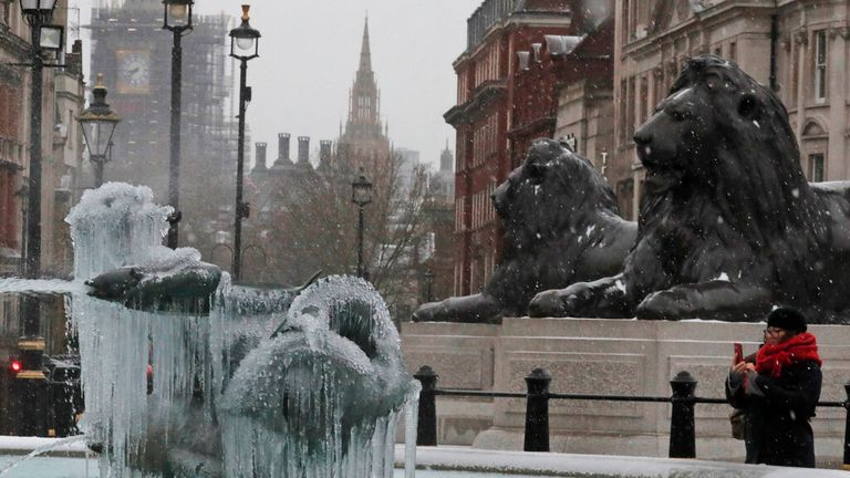 A woman takes pictures of icicles on the fountain in Trafalgar Square with the background of Big Ben as temperatures dropped below freezing in London, Tuesday, Feb. 9, 2021. Snow has swept across the country, with further snowfall predicted, bringing travel problems as temperatures dropped. (AP Photo/Frank Augstein)