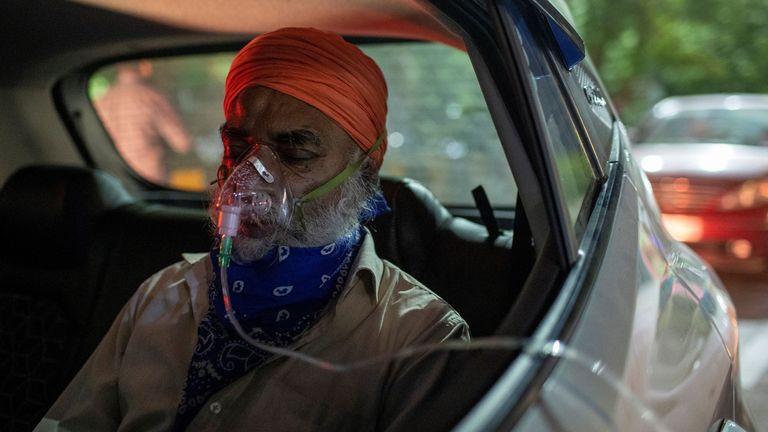 Seorang pria menerima bantuan oksigen secara gratis di dalam mobilnya di Gurudwara (kuil Sikh) di Ghaziabad, India. Foto: Reuters