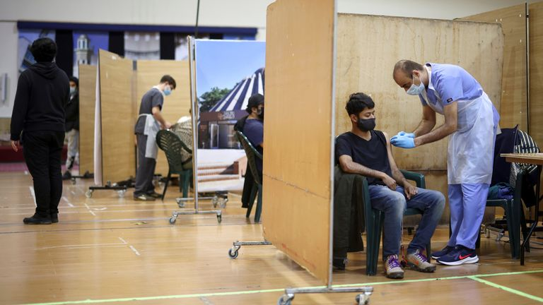 A man receives an AstraZeneca jab at a coronavirus vaccination centre in London's Baitul Futuh Mosque