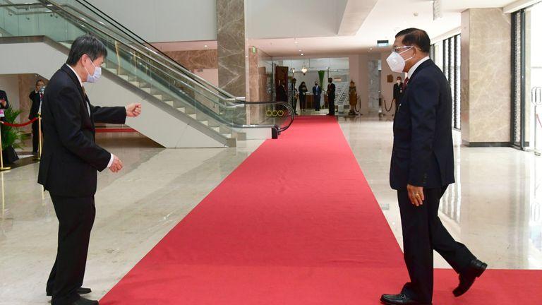 Myanmar's junta chief Senior General Min Aung Hlaing (R) is welcomed to the summit by ASEAN Secretary General Lim Jock Hoi