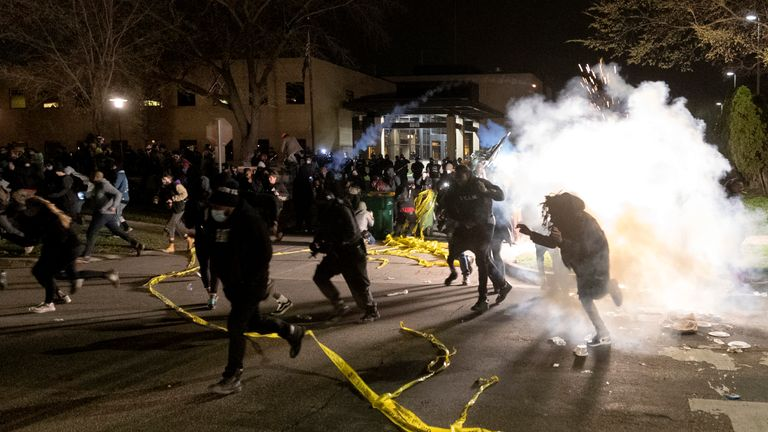 Police attempt to disperse the crowds outside Brooklyn Center Police Department building on Sunday night