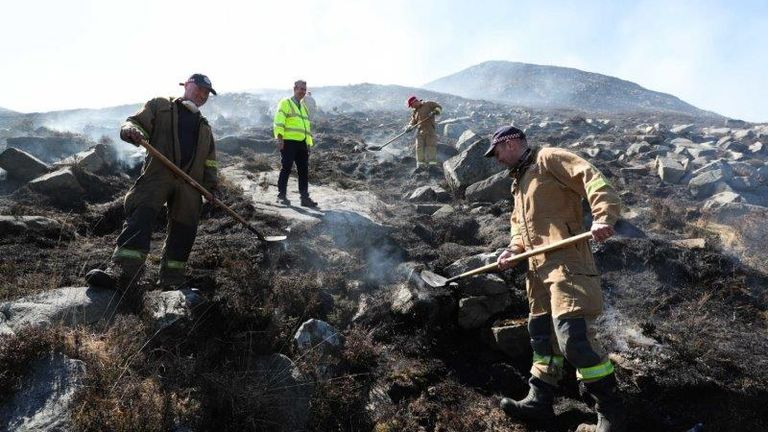 Firefighters among the burned out gorse in the Mourne Mountains. Pic: Department of Agriculture via PA