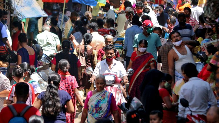 People are seen at a crowded marketplace in a slum area of Mumbai