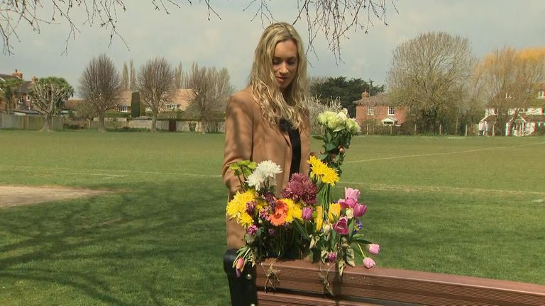 Sue Redman places flowers on Kelly Fitzgibbons' memorial bench