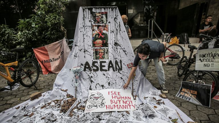 A woman prepares a placard with crossed out portraits of Myanmar's junta chief Senior General Min Aung Hlaing during a protest in Jakarta, Indonesia against his military coup