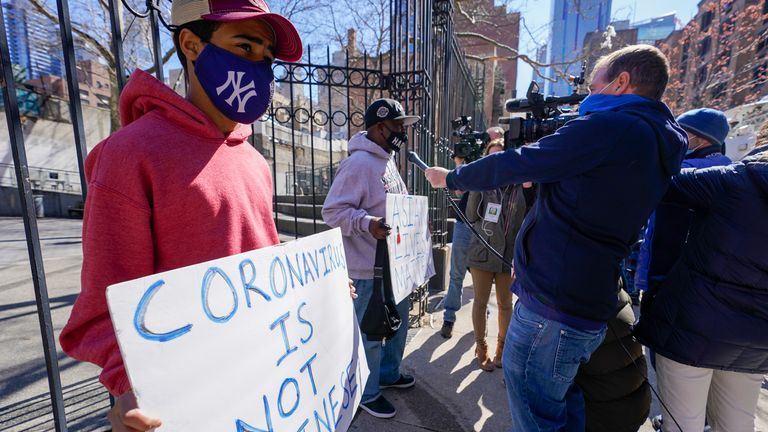 Community activists Calvin, right, and Cameron Hunt speak to reporters outside the building where an Asian American woman was assaulted