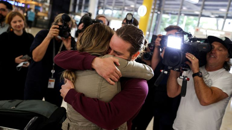 Adam Draper and his partner Stacey Brown embrace each other as she arrives from New Zealand