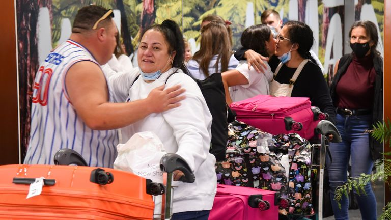 Families and loved ones embrace after arriving on the first Air New Zealand flight