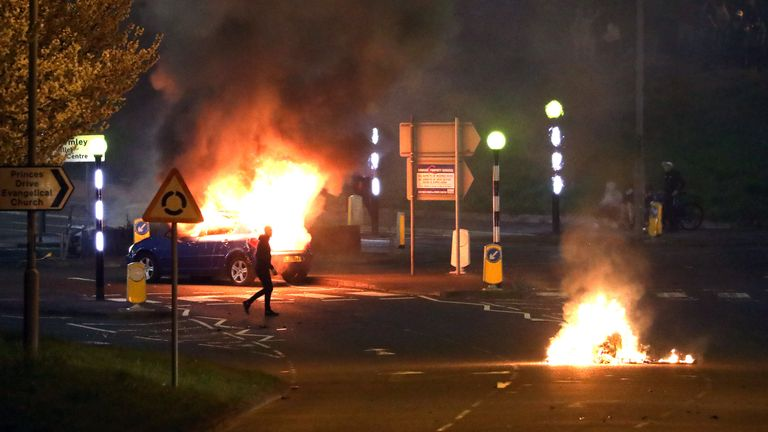 A man walks past a burning car that was hijacked by Loyalists at the Cloughfern roundabout in Newtownabbey