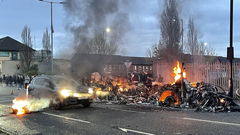 A car drives past the wreckage of a Translink Metrobus on fire on the Shankill Road in Belfast during further unrest. Picture date: Wednesday April 7, 2021.