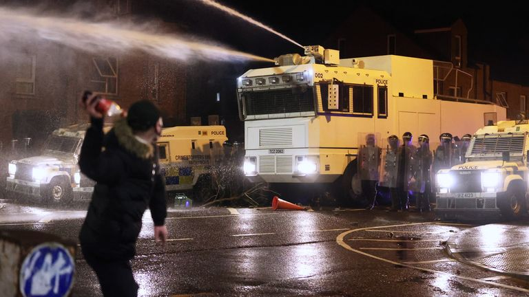 Objects are thrown towards PSNI officers and the water canon on Springfield Road in Belfast during further unrest. Picture date: Thursday April 8, 2021.
