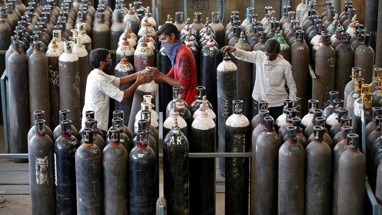 Men carry oxygen cylinders after refilling them in a factory in Ahmedabad