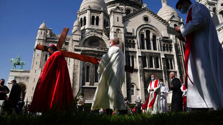 Paris Archbishop Michel Aupetit carries the holy cross at the Way of the Cross ceremony as part of the Holy Easter celebration
