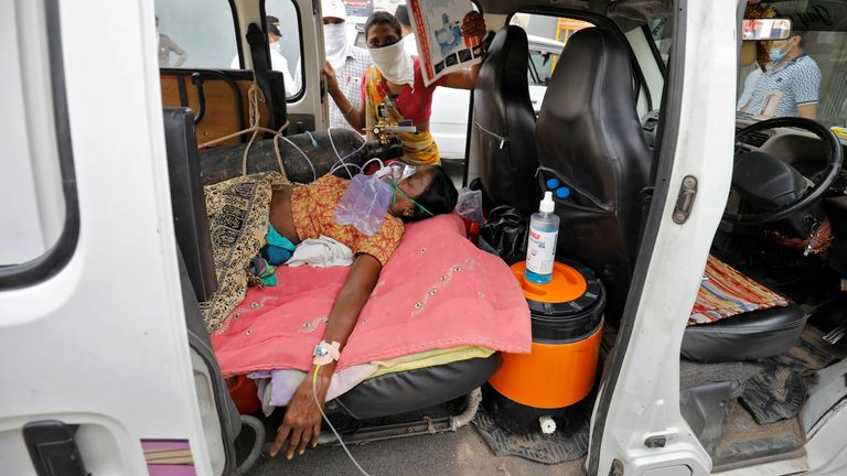 A patient wearing an oxygen mask inside a car, waiting to enter a hospital in Ahmedabad, India. Pic: Reuters