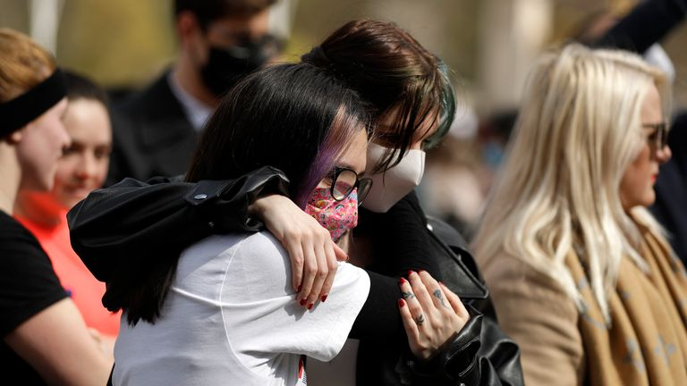 Two people console each other in front of the gate at Buckingham Palace in London. Pic: AP