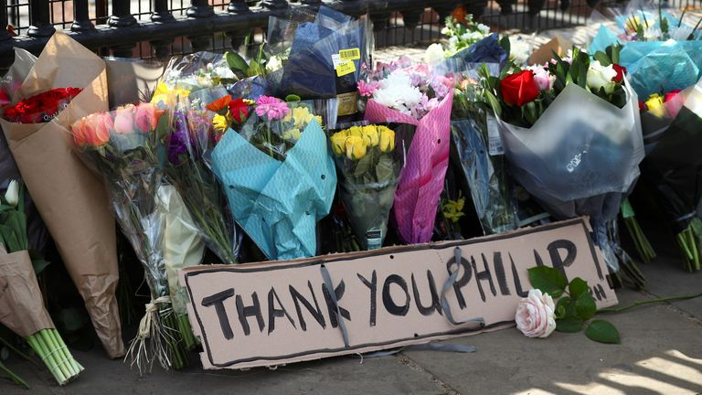 Bouquets of flowers are laid down outside Buckingham Palace