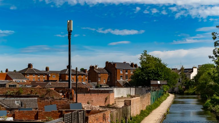 Shot showing a mobile cell tower in the middle of a down town housing estate - close to homes.
