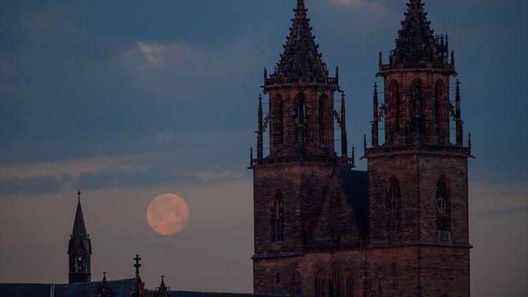 La luna tramonta dietro la cattedrale della capitale dello stato in Sassonia-Anhalt, Magdeburgo.  Pic: AP