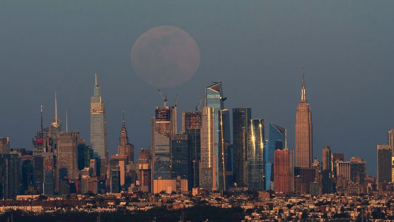 "Luna piena, comunemente nota come ""Super Pink Moon"", Sorgendo sopra lo skyline di New York e l'Empire State Building, visto da West Orange, nel New Jersey, USA, 26 aprile 2021. Reuters / Eduardo Munoz"