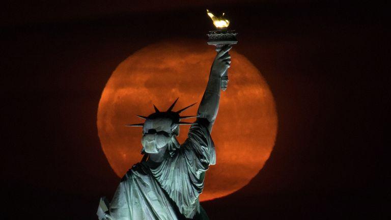 """Luna piena, comunemente nota come """"Super Pink Moon"""" Sorge dietro la Statua della Libertà a New York City, USA, il 27 aprile 2021. REUTERS / Bjorn Kells / New York Mediaboat NESSUNA RIVENDITA.  Non archiviare"""