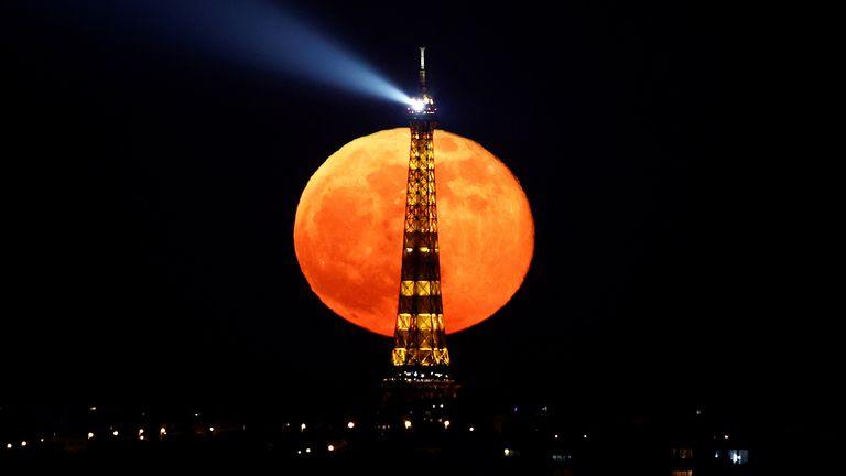 """Luna piena, comunemente nota come """"Super Pink Moon"""" Sorge dietro la Torre Eiffel durante un coprifuoco nazionale a causa di misure più severe contro la diffusione della malattia del Coronavirus (COVID-19) a Parigi, Francia, 27 aprile 2021. REUTERS / Christian Hartmann TPX IMMAGINI DEL GIORNO"""