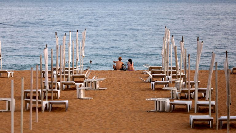 A couple is seen next to rows of empty hammocks during the coronavirus pandemic in Albufeira, Portugal REUTERS/Rafael Marchante/File Photo