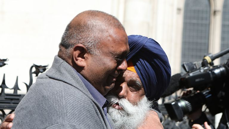 Former post office worker Harjinder Butoy (left) hugs his father outside the Royal Courts of Justice