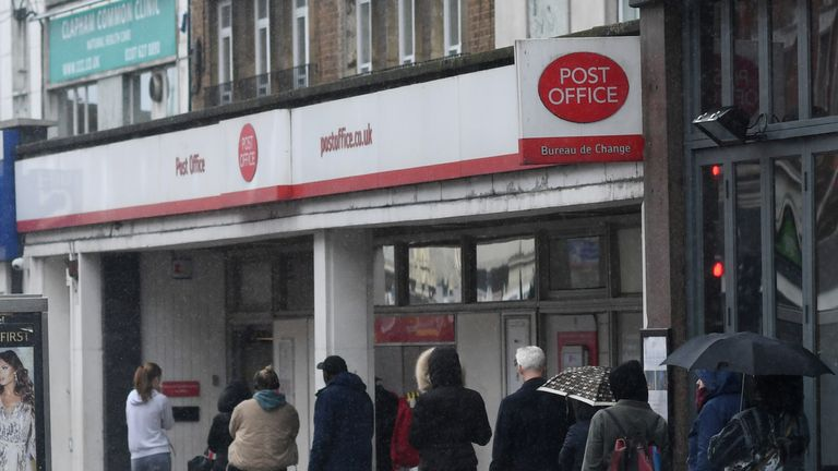 The spread of the coronavirus disease (COVID-19) in London People queue for a Post Office on Clapham high street as the spread of the coronavirus disease (COVID-19) continues, London, Britain, March 30, 2020. REUTERS/Dylan Martinez