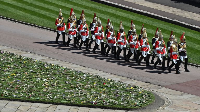 Military in parade dress uniform march past flowers. Pic: AP