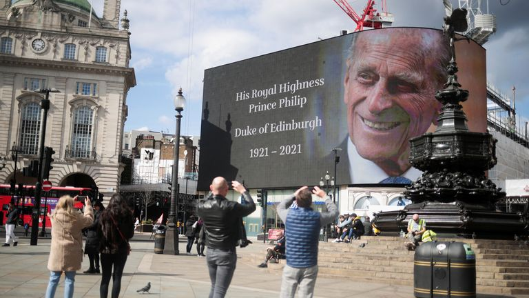 People take pictures of a screen with a picture and a message about Prince Philip