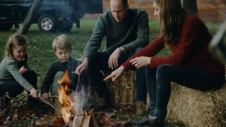 The couple and their children are pictured around a campfire in one part of the clip