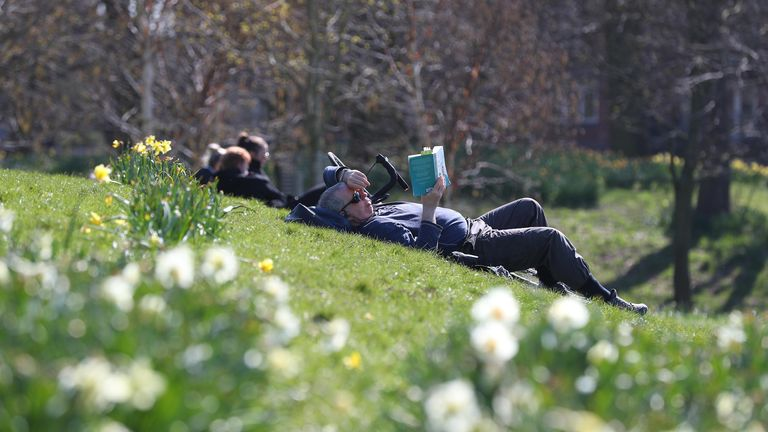 Someone lazing with a book in Sefton Park, Liverpool, on Sunday