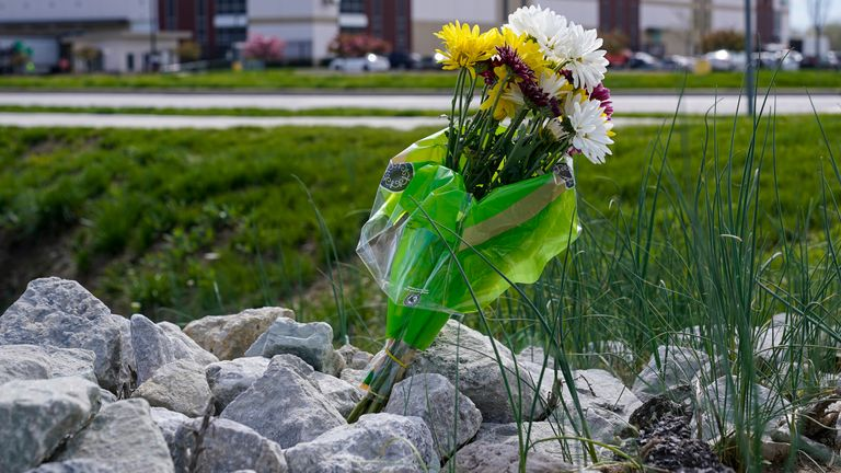 A single bouquet of flower sits in the rocks across the street from the FedEx facility in Indianapolis. Pic: AP
