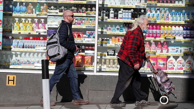 People walk pas a store, as coronavirus disease (COVID-19) lockdown restrictions begin to ease, in Newcastle upon Tyne, Britain, April 12, 2021. REUTERS/Lee Smith