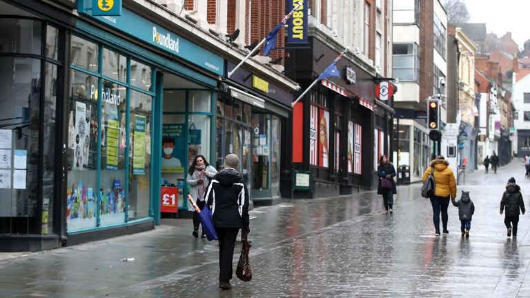 Shoppers walk past closed shops and Poundland in Lincoln city centre