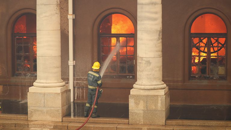 Firefighters battle flames as the library at the University of Cape Town burns after fire broke out on the slopes of Table Mountain in Cape Town