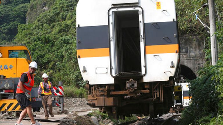 Rescue workers remove a part of the derailed train near Taroko Gorge in Hualien, Taiwan