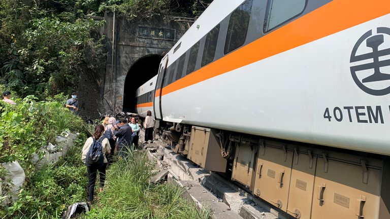 People walk next to a train which derailed in a tunnel north of Hualien, Taiwan April 2, 2021, in this handout image provided by Taiwan's National Fire Agency. Taiwan's National Fire Agency/Handout via REUTERS ATTENTION EDITORS - THIS IMAGE WAS PROVIDED BY A THIRD PARTY. NO RESALES. NO ARCHIVES.