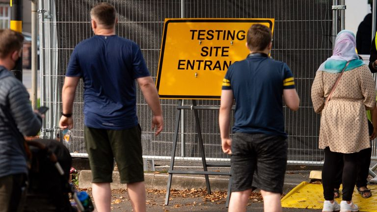 Personas hacen cola en una instalación de pruebas de coronavirus en Sutton Coldfield, Birmingham