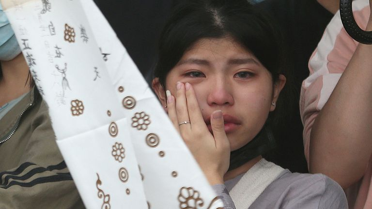 The families of the victims cry as conjure their spirits near Taroko Gorge in Hualien, Taiwan on Saturday, April 3, 2021. The train partially derailed in eastern Taiwan on Friday after colliding with an unmanned vehicle that had rolled down a hill, killing and injuring dozens. (AP Photo/Chiang Ying-ying)