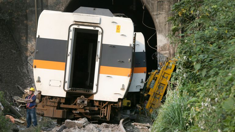 This photo show, the trouble-causing car flip over to the right of. the derailed train near Taroko Gorge in Hualien, Taiwan on Saturday, April 3, 2021. The train partially derailed in eastern Taiwan on Friday after colliding with an unmanned vehicle that had rolled down a hill, killing and injuring dozens. (AP Photo/Chiang Ying-ying)