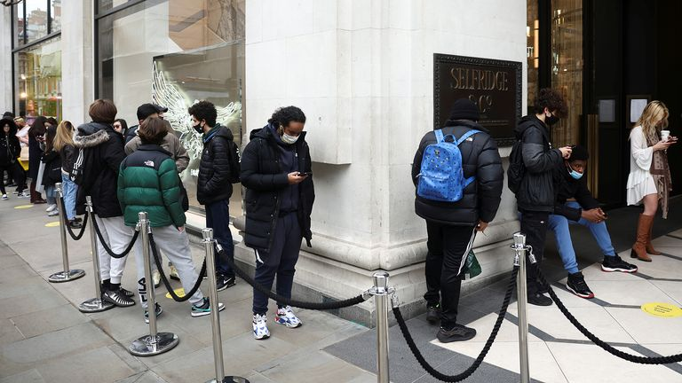 People queue outside a shop, as the coronavirus disease (COVID-19) restrictions ease, in London, Britain April 12, 2021. REUTERS/Henry Nicholls